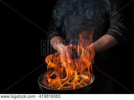 Chef Or Cook Cooking Food In Pan With Fire Flame On Black Background. Restaurant And Hotel Service C