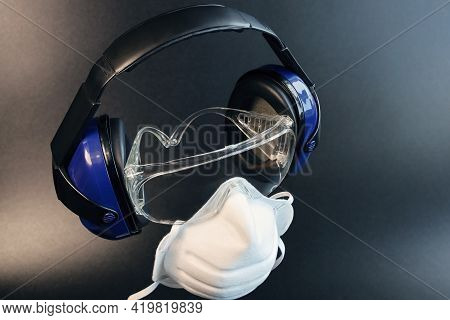 Individual Protective Equipment, Headphones And Glasses With Respiratory Filtering Mask, On Dark Bac
