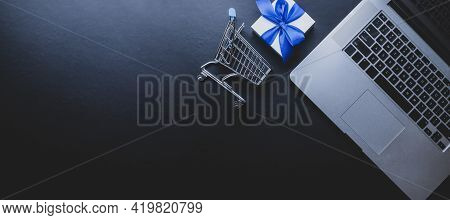 Ecommerce. Laptop Computer, Shopping Trolley And White Gift With Blue Ribbon On Dark Background. Web