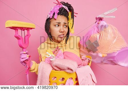 Home Cleaning Concept. Dissatisfied Dark Skinned Afro American Woman Looks Unhappily At Trash Bag Ho