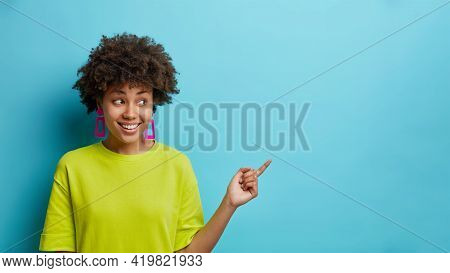 Pleased Dark Skinned Woman Points Right On Promo Offer Shows Logo Banner Recommends Click On Link We