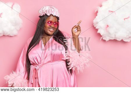 Horizontal Shot Of Pleased Dark Skinned Obese Woman Wears Shower Cap And Dressing Gown Indicates At
