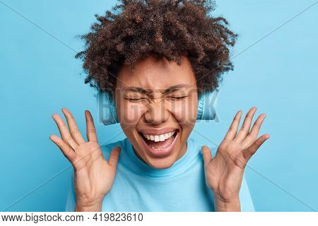 Overjoyed Afro American Woman Keeps Hands Raised Exclaims Joyfully Closes Eyes From Happiness Reacts