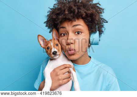 Lovely African American Woman Carries Small Breed Dog Near Face Keeps Lips Folded As If Wanting To K