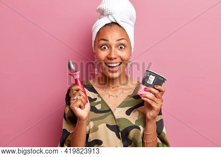 Indoor Shot Of Happy Surprised Female Model Holds Spoon And Ice Cream In Bucket Enjoys Eating Frozen