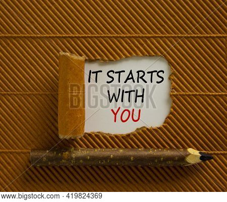 It Starts With You Symbol. Words 'it Starts With You' Appearing Behind Torn Brown Paper. Beautiful B