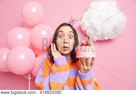 Impressed Stupefied Asian Woman Wears Princess Crown And Jumper Dresses For Birthday Party Holds Del