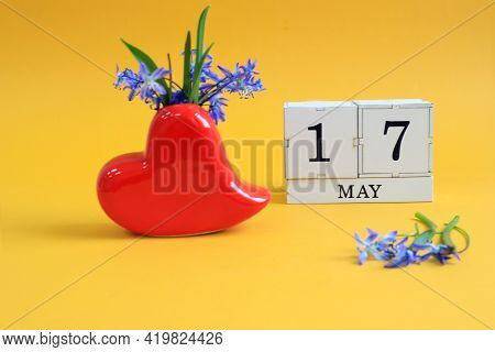 Calendar For May 17 : A Bouquet In A Heart-shaped Vase With Blue Flowers And The Numbers 17 On Cubes