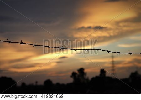 Closeup Of Barbed Wires Protecting Boundaries Against Golden Glow An Evening Sky