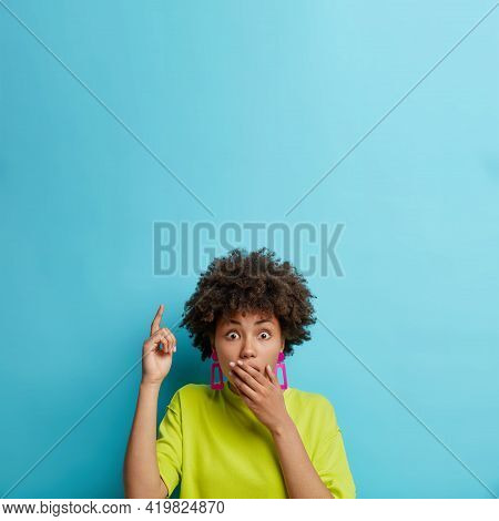 Shocked Curly Haired Woman Covers Mouth Points Index Finger Upwards Stares Puzzled Indicates At Logo