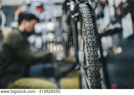 Bicycle Shop Repairman Works In Bicycle Service And Repair Workshop During Coronavirus Quarantine We