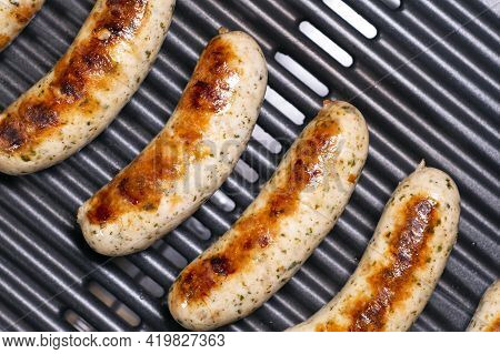 Delicious German Sausages On The Barbecue Electro Grill. Tasty Sausages Sizzling On A Portable Elect