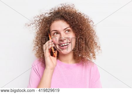 Positive Woman With Natural Curly Hair Calls Friend To Meet Up Holds Smartphone Near Ear Looks Upwar