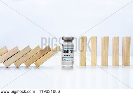 Wooden Pieces Domino Effect Stopping Fall With A Covid-19 Vial Vaccine, Next To Stand Wooden Pieces