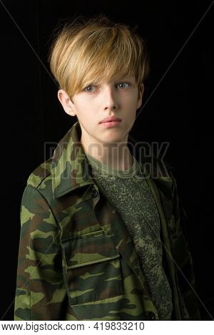 Confident Teenage Boy In Camouflage Clothing. Teenager In Khaki Military Clothing Posing On Black Ba