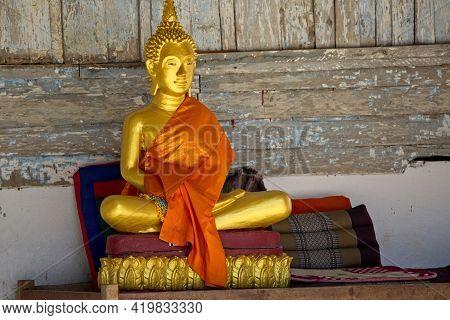 Golden Statute Of Buddha Sitting With Orange Robe In Monastery Luang Prabang, Laos.
