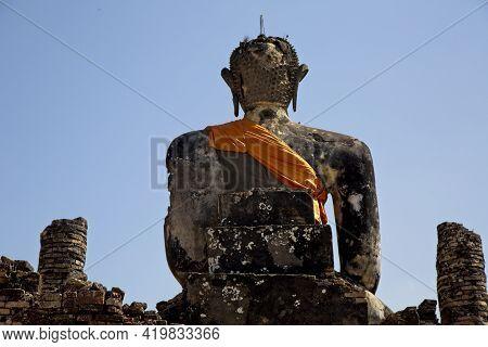 Huge Stone Statute Of Buddha Wrapped In Orange Clock Monastry Phonsavan, Laos.
