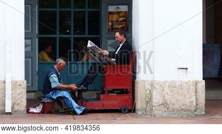 Cuenca, Ecuador - February 21, 2020: Unidentified Ecuadorian Man Shoe Shine Worker Cleans The Other