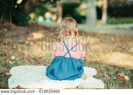 Sad Upset Baby Kid Sitting On Ground Outdoors In Park. Child Got Offended. Upset Innocent Baby Girl