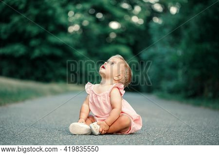 Surprised Curious Caucasian Happy Baby Girl Sitting On Ground Empty Road Outdoor Looking Up. Funny C