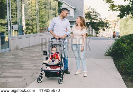 Caucasian Mother And Father Walking With Baby Daughter In Stroller. Family Strolling Together Outdoo