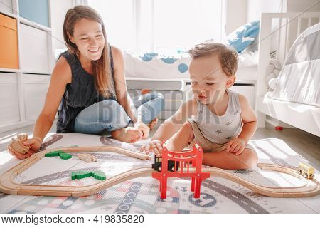 Mother And Toddler Boy Playing With Car Wooden Railway On Floor At Home. Early Age Education Develop