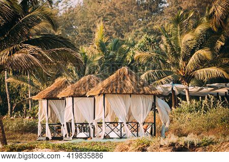 Goa, India. Gazebo Tents With Strawing Roof For Tourists On Beach With Tables And Sunbeds Inside.