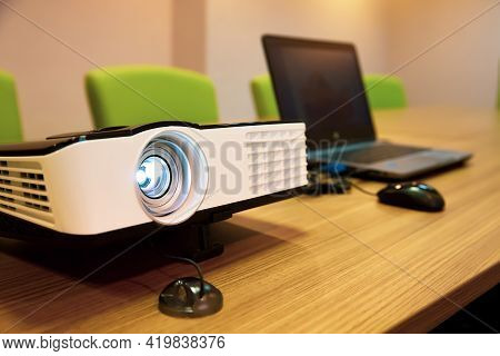 Close Up Computer Projector On Meeting Tables With Laptop Setup At Boardroom Or Seminar Or Classroom
