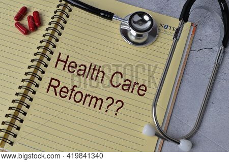 Top View Of Stethoscope, Pill Capsules And Notebook Written With Text Healthcare Reform?
