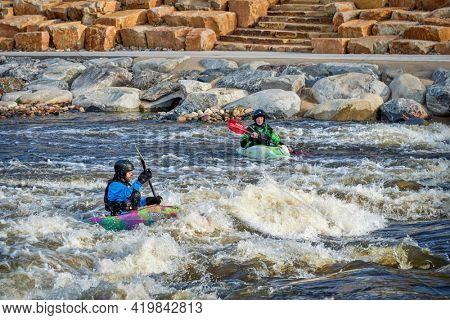 Fort Collins, CO, USA - May 7, 2021: Young male kayakers surfing a wave in the Poudre River Whitewater Park.