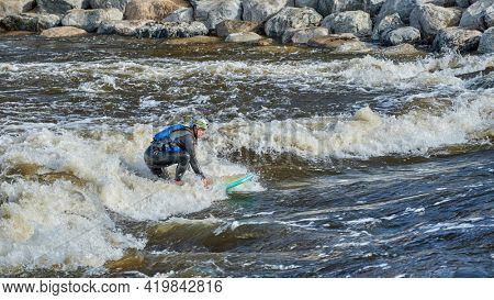 Fort Collins, CO, USA - May 7, 2021: Paddleboard paddling is surfing a wave in the Poudre River Whitewater Park.