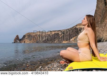 Young Woman In Beige Sportswear With Long Hair Practicing Stretching Outdoors On Yoga Mat By The Sea