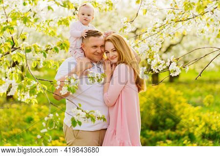 Family With A Baby Daughter In Spring Flowering Garden. Cleft Lip In Infants.