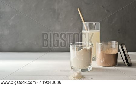 Whey Protein Drink In A Glass And Jars With Protein Powder On Beige Background. Chocolate And Vanill