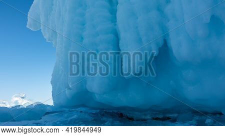 The Base Of The Rock On The Frozen Lake, Close-up. Thick Bizarre Icicles Hang From The Steep Slopes.