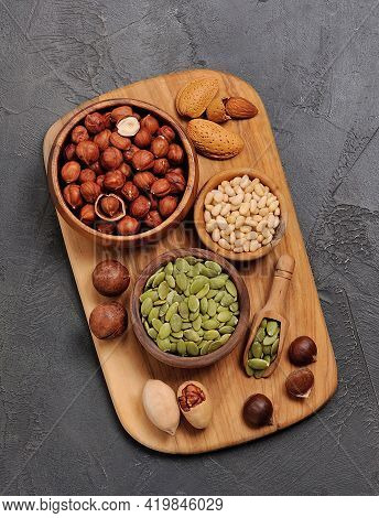 Assorts Of Nuts Closeup On Board . Nuts Of Almonds, Filbert, Pine, Macadami And Pumpkin Seed.