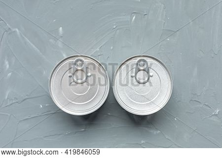 Two Tin Canned Food, No Label On Gray Background. Provisions Or Cat Food Concept. Close Up, Top View