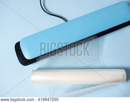 Close-up Of A Blue Vacuum Packer On A Bright Blue Background. Next To The Packaging Bags. A Machine