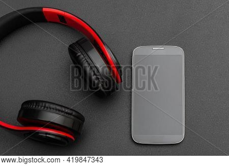 Bluetooth Headphones With Smartphone On A Black.