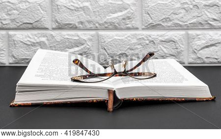 Opened Book With Eyeglasses On Black Table.