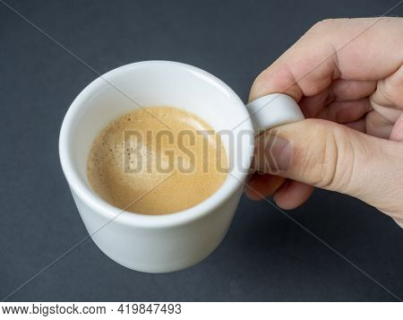 A Man's Hand Holds A White Cup Of Freshly Brewed Espresso On A Dark Background. Brown Foam. An Invig