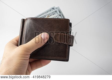 A Man's Hand Holds A Brown Leather Wallet With 100 Dollars Bills Sticking Out Of It On A White Backg