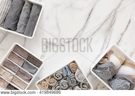 Neatly And Tidy Folded Lingeries In Organizer Drawer Divider On White Marble Background.