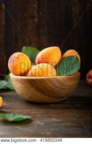 Ripe Apricots And Apricot Leaves In A Bowl On A Wooden Table. Fresh Fruits From The Home Garden. Hea