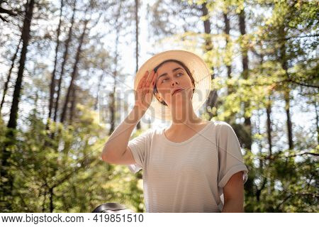 Portrait Of A Young Woman In A Straw Hat, Wiping Sweat From Her Forehead. Summer. The Concept Of Pro