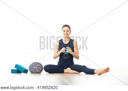 Restorative Yoga With A Bolster. Young Sporty Female Yoga Instructor In Bright White Yoga Studio, Sm