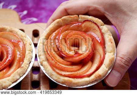 Man's Hands Placing A Fresh Baked Delectable Mini Apple Rose Tartlet On The Wooden Breadboard