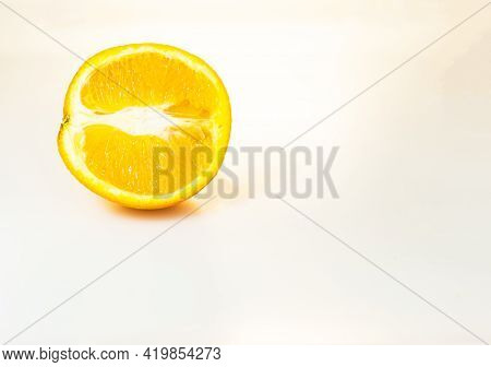 One Half Of A Yellow Juicy Orange In Artificial Light On The Left Side Of The Frame