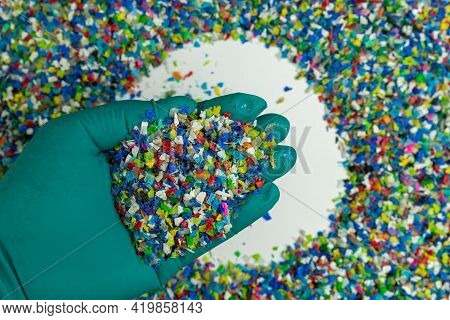 Crushed Plastic On Green Gloved Hand. Reuse Of Plastic. Polymer Beads. Scraps Obtained From Plastic