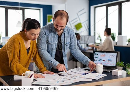 Busy Diverse Employees Analysing Annual Statistics In Front Of Laptop